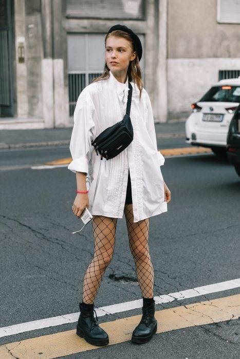 chica con camisa blanca boina negra y medias de red