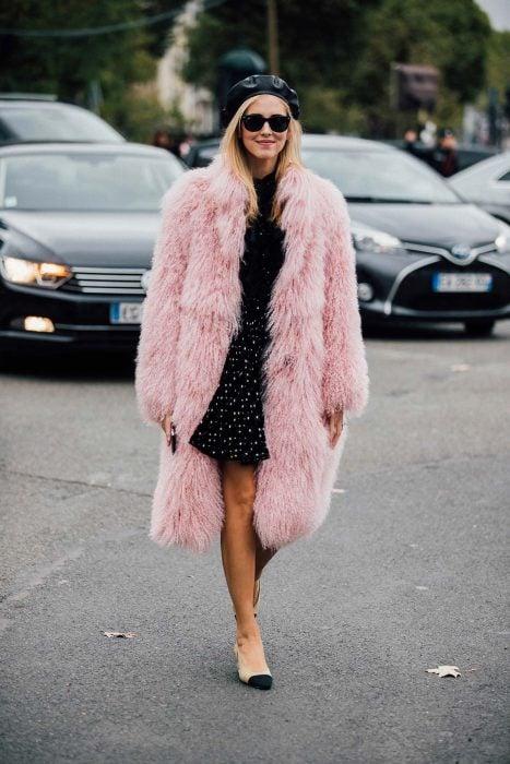 chica con falda de lunares, blusa negra y abrigo peludo rosa con boina negra
