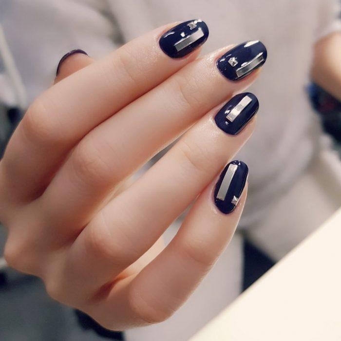 manicura de uñas negras con piedras doradas