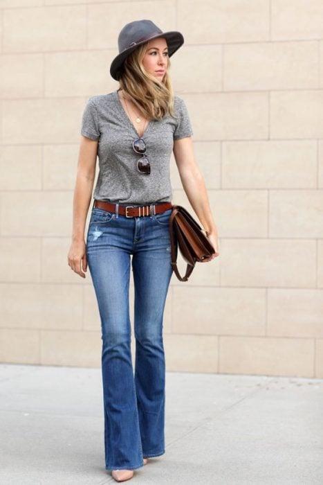 chica con blusa gris pantalones de campana cinto