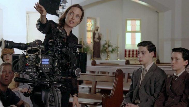 Angelina jolie junto a una camara dirigiendo una película