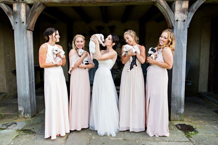 Damas de honor jugando con unos cachorros durante una sesión de fotos