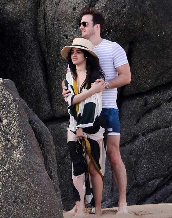 Pareja de novios abrazados en la playa