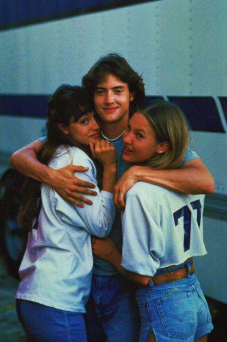 chico de cabello largo abrazando a dos chicas