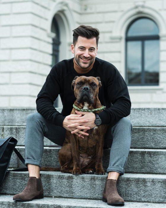 Chico sosteniendo a su perro y haciendo caras graciosas