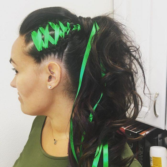 Chica usando una trenza de corset tejida con listones de color verde neón y una coleta alta para terminarlas