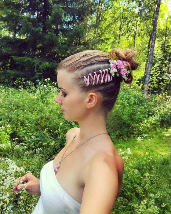 Chica usando unas corset braide lateral rejida con un listón en color rosa y aplicaciones de florería