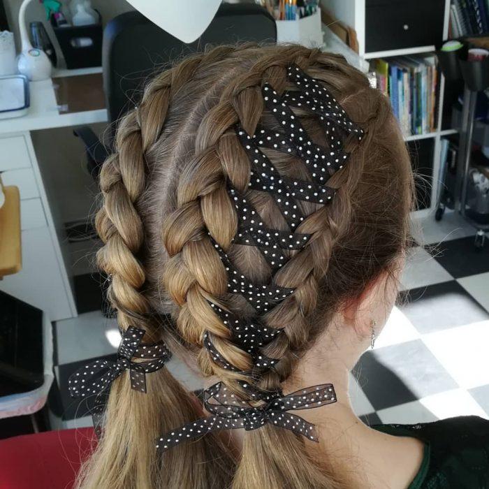 Chica usando unas corset braides dobles u adornadas con un listón negro y con puntos blancos