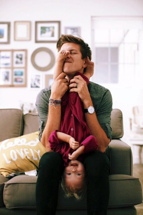 padre e hija jugando a las cosquillas