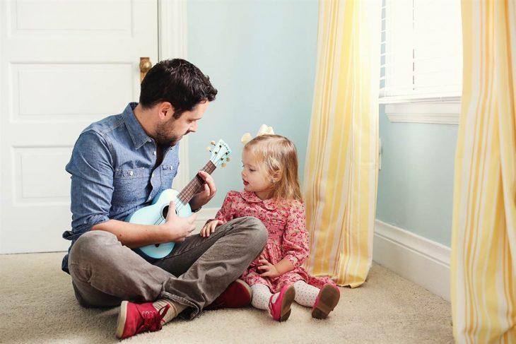 hombre cantándole a su hija con una guitarra