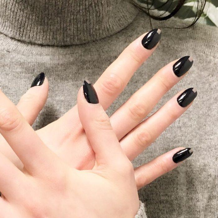 Uñas de almendra en tonos negros con una aplicación de color café