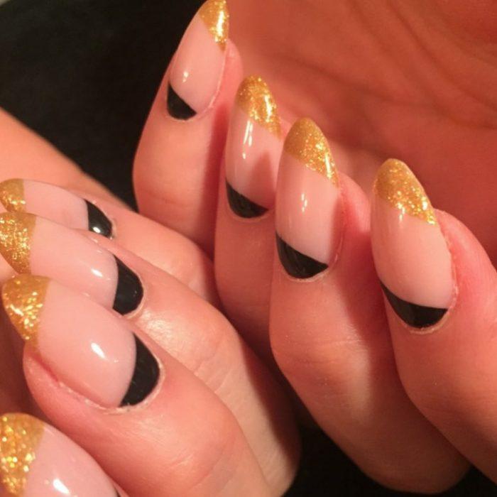 Uñas de almendra en tonos dorados con negro