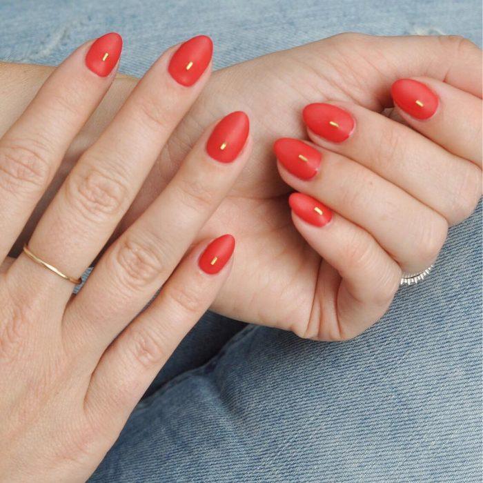 Uñas de almendra en tonos rojos con una aplicación color oro