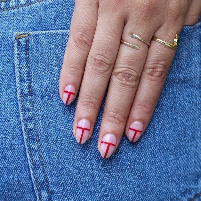 Uñas de almendra en tonos naturales con unas líneas de color rojo