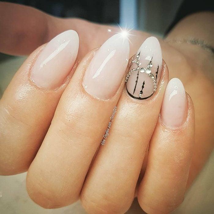 Uñas de almendra en tono nude con aplicaciones de piedras
