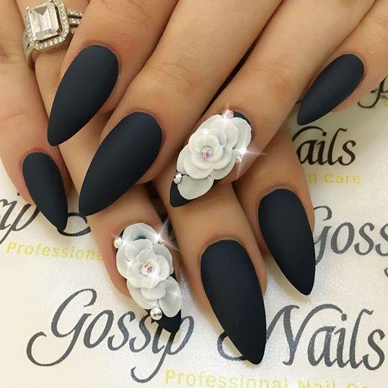 Uñas de almendra en tonos negro mate con una rosa