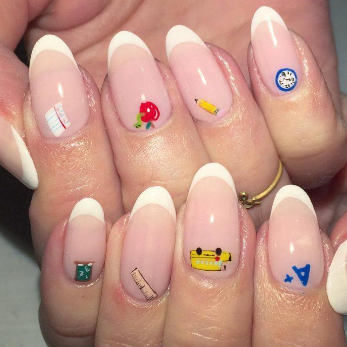 Diseño de uñas francesas en color blanco con aplicaciones de calcomanías