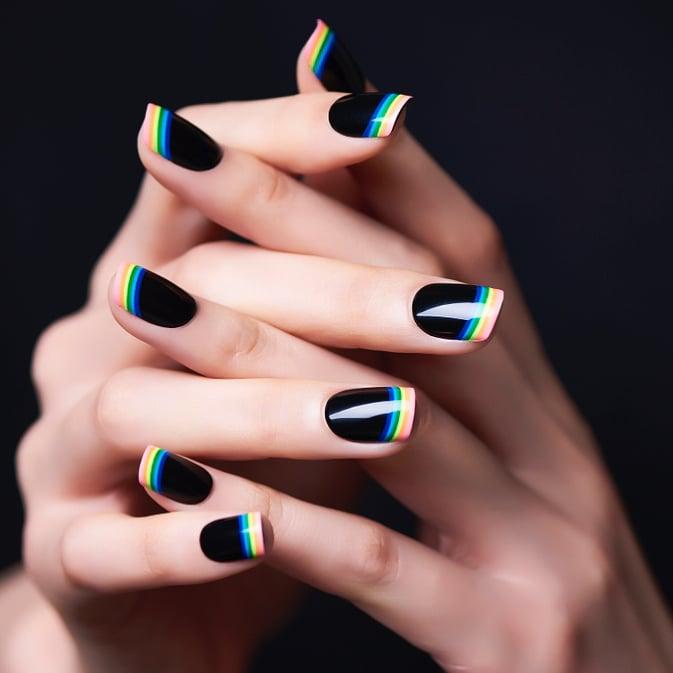 Diseño de uñas en color negro con líneas que simulan el arcoíris