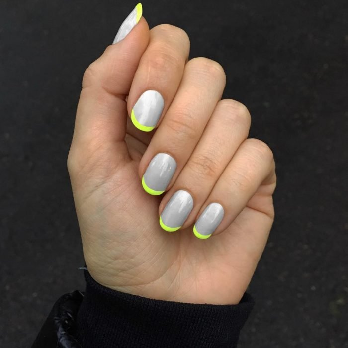 Diseños de uñas en color gris con una línea color amarillo neón