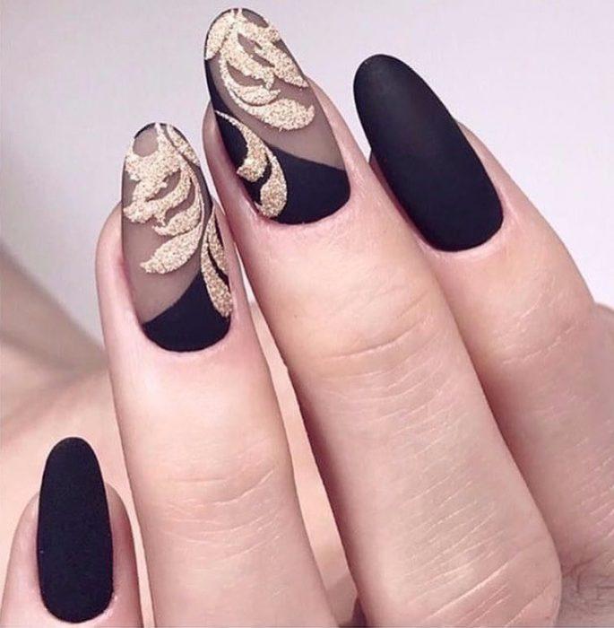 Uñas de stilletto con diseño de color negro con toques dorados