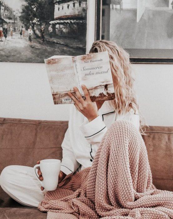 chica con pijama blanca leyendo y bebiendo té
