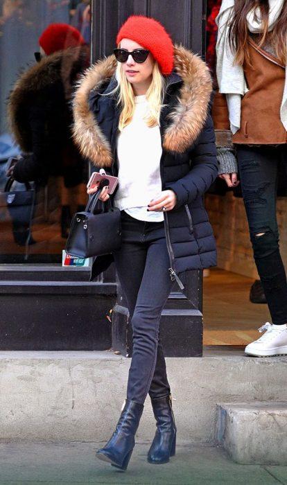 Emma Roberts caminando por la calle mientras usa una casadora negra y pantalones negros