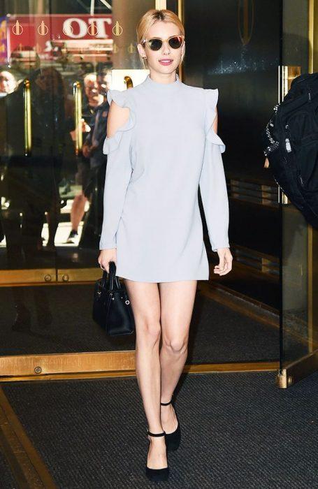 Emma Roberts caminando por la calle mientras usa un vestido gris sin mangas