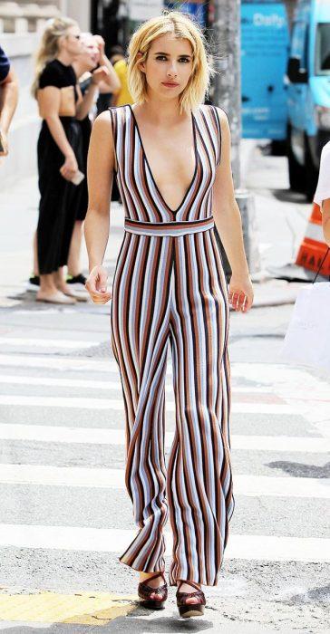 Emma Roberts caminando por la calle mientras usa un mono a rayas