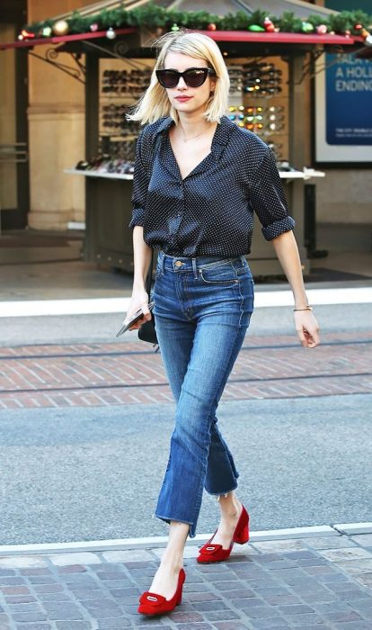 Emma Roberts caminando por la calle mientras usa una blusa negra con jeans y zapatos rojos