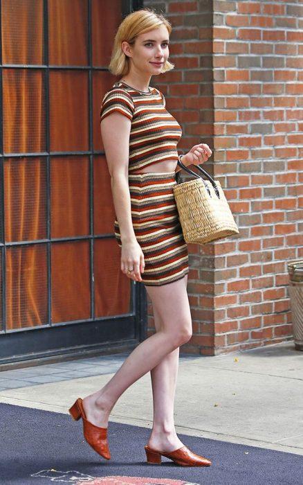Emma Roberts caminando por la calle mientras usa un vestido a rayas