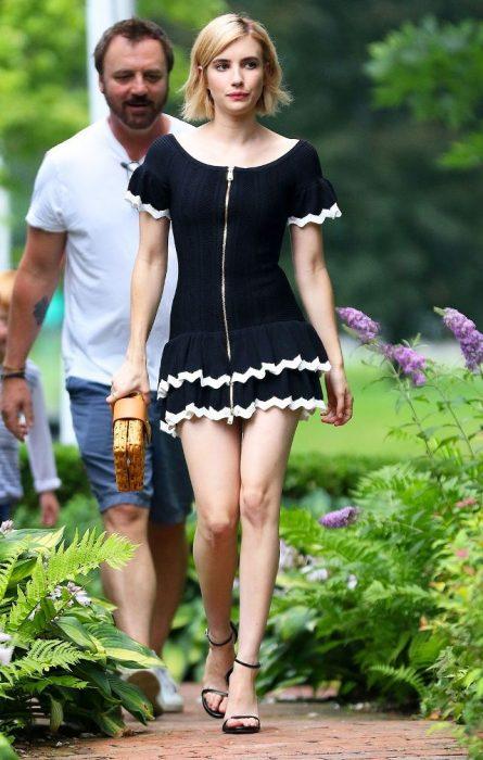 Emma Roberts caminando por la calle mientras usa un vestido negro con olanes