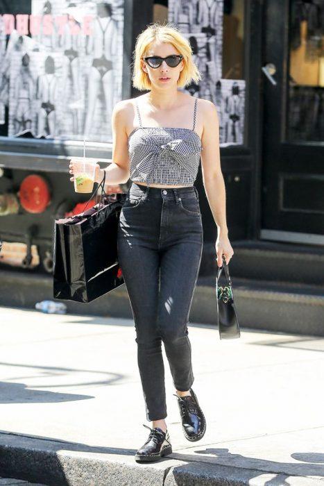 Emma Roberts caminando por la calle mientras usa un pantalón negro y una blusa de color gris