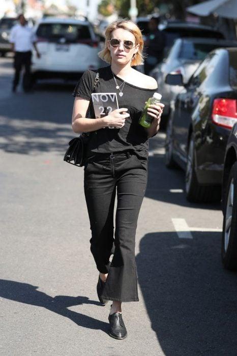 Emma Roberts caminando por la calle mientras usa un conjunto de color negro