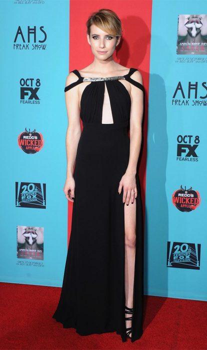 Emma Roberts caminando por la calle mientras usa un vestido de gala color negro con perlas