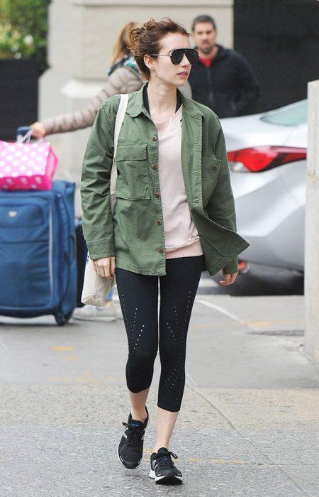 Emma Roberts caminando por la calle mientras usa una casadora verde y leggings