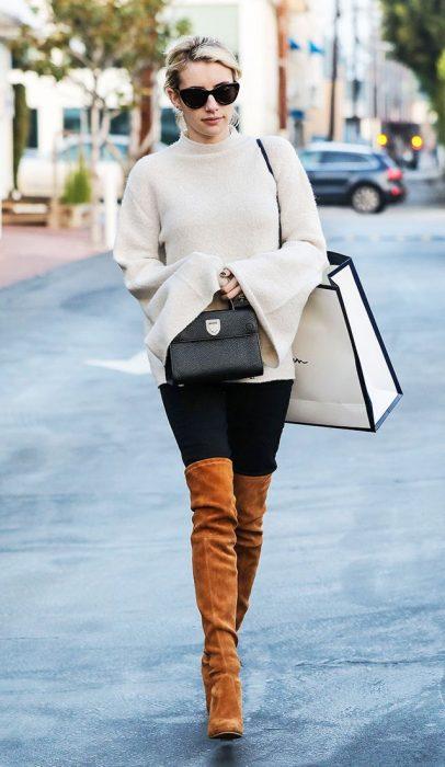 Emma Roberts caminando por la calle mientras usa un sueter largo y botas hasta el muslo