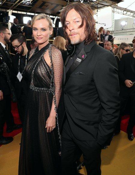 Diane Kruger y Norman Reedus posando para una foto en una alfombra roja