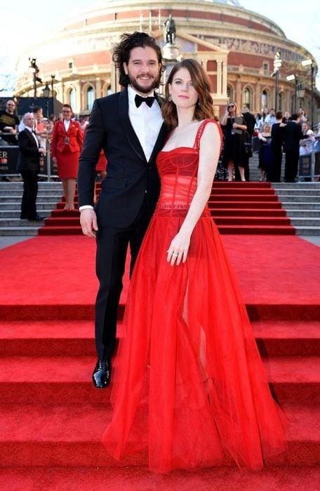 Kit Harrigton y su novia posando en una alfombra roja