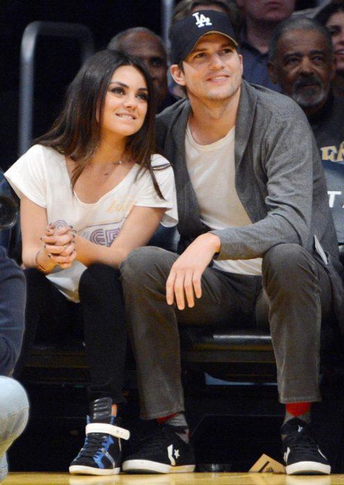 Mila kunis y Ashton Kutcher viendo un juego de baloncesto