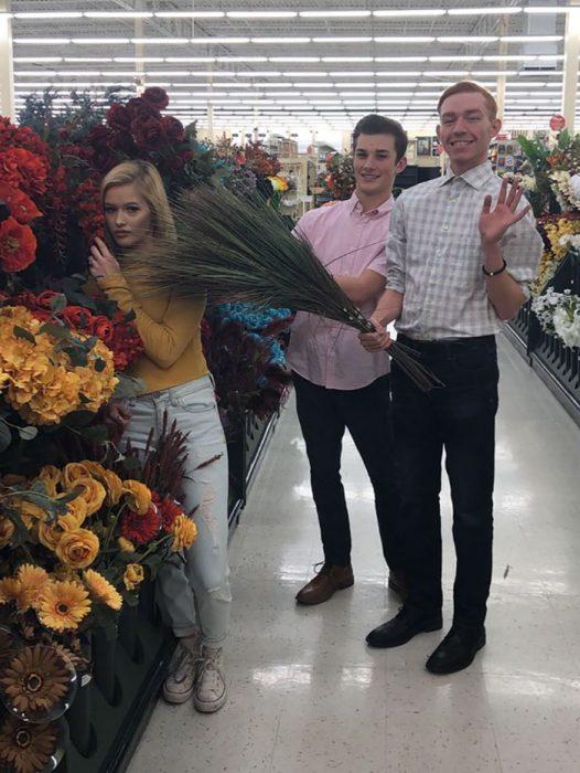 Chica recargada sobre flores sinteticas durante una sesión de fotos