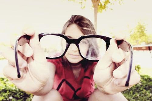 Chica sosteniendo unos lentes sucios