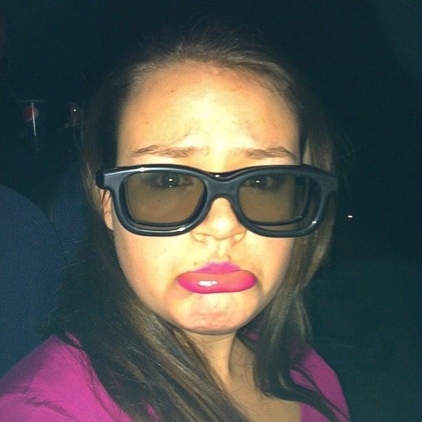 Chica poniendo sus lentes normales sobre otros lentes para ver películas en 3D