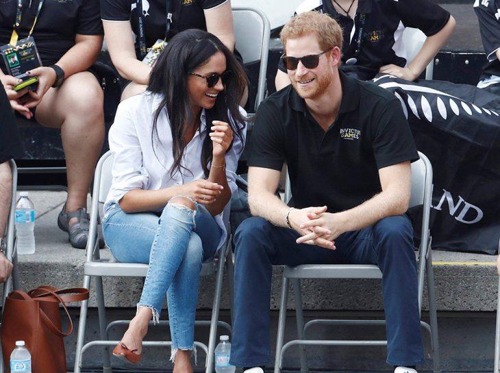 Meghan Markle usando unos zapatos flats de color café mientras está sentada junto al principe harry