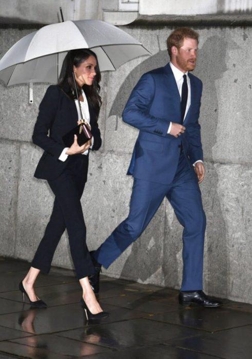 Meghan Markle y el príncipe Harry caminando bajo la lluvia