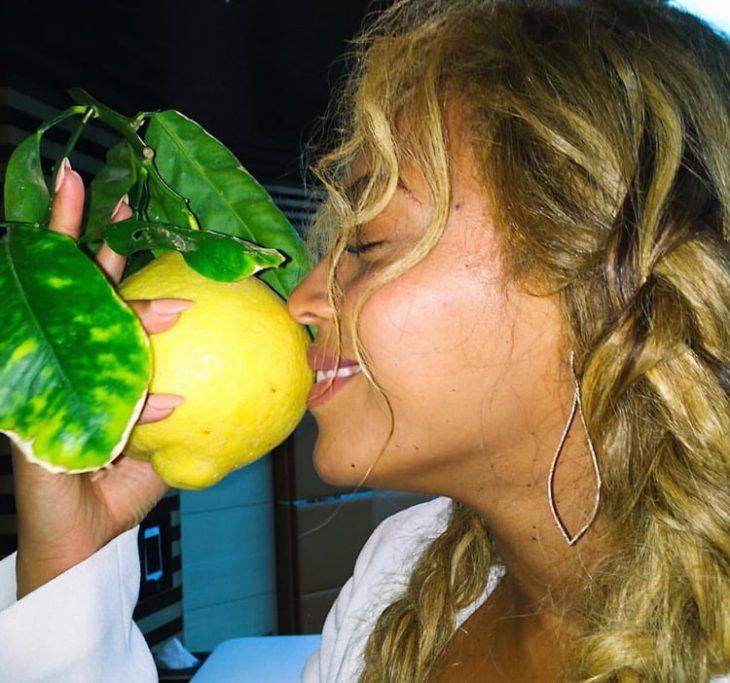 chica oliendo un limón