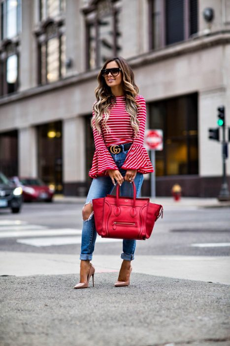 Chica usando unos skinny jeans, blusa y bolsa roja