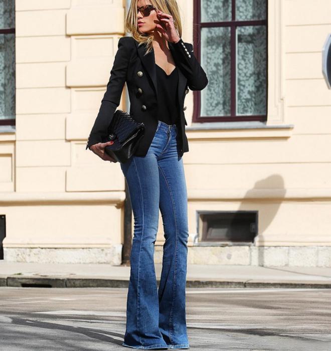 Chica usando unos jeans acampanados y un blazer negro