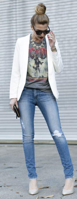 Chica usando una blusa estampada, un blazer y jean rasgado