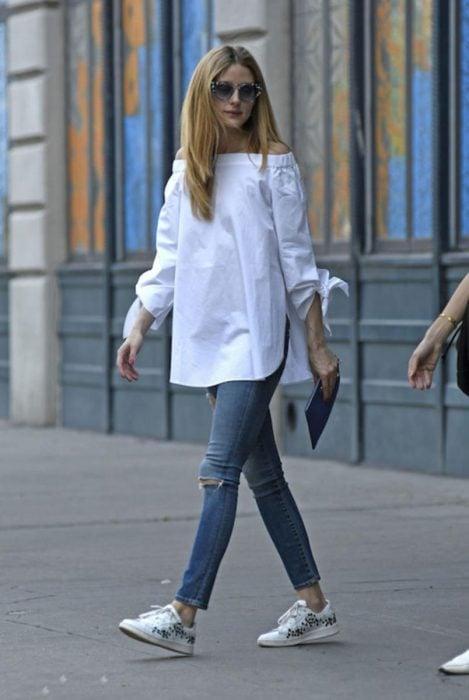 Chica usando unos jeans azules y una camisa sin hombros