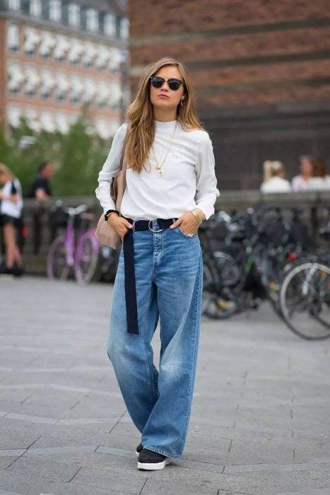 Chica usando unos jeans acampanados y una camisa blanca